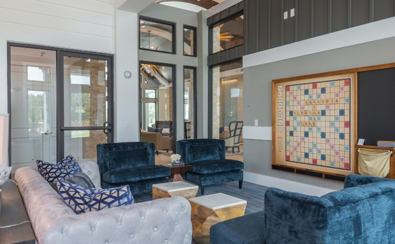 Clubhouse with plush sofa seating and large scrabble on wall.